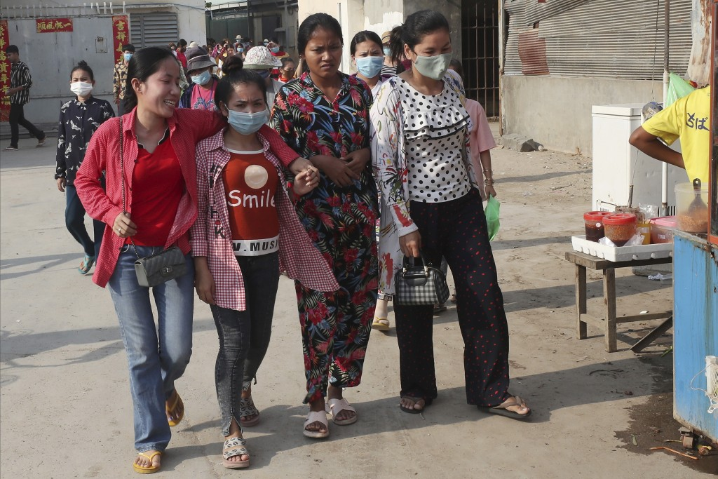 In this March 20, 2020, photo, garment factory workers wear face masks as they walk out at the end of their work shift near Phnom Penh, Cambodia. May ...
