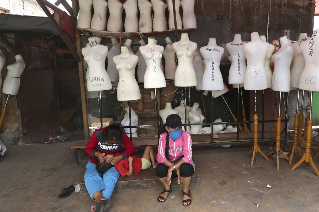In this Thursday, April 30, 2020, photo, Indonesian women sit among mannequins at Tanah Abang textile market that is closed due to the new coronavirus...