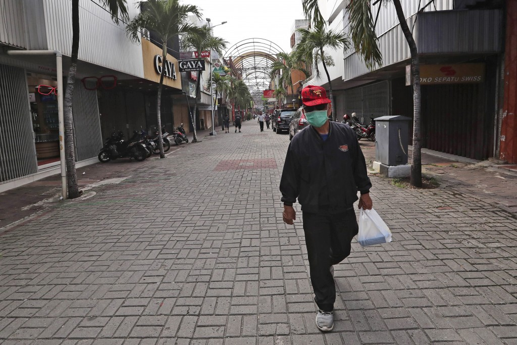 In this Thursday, April 30, 2020, photo, a man walks past rows of shops closed due to the new coronavirus outbreak at Pasar Baru Shopping Center that ...