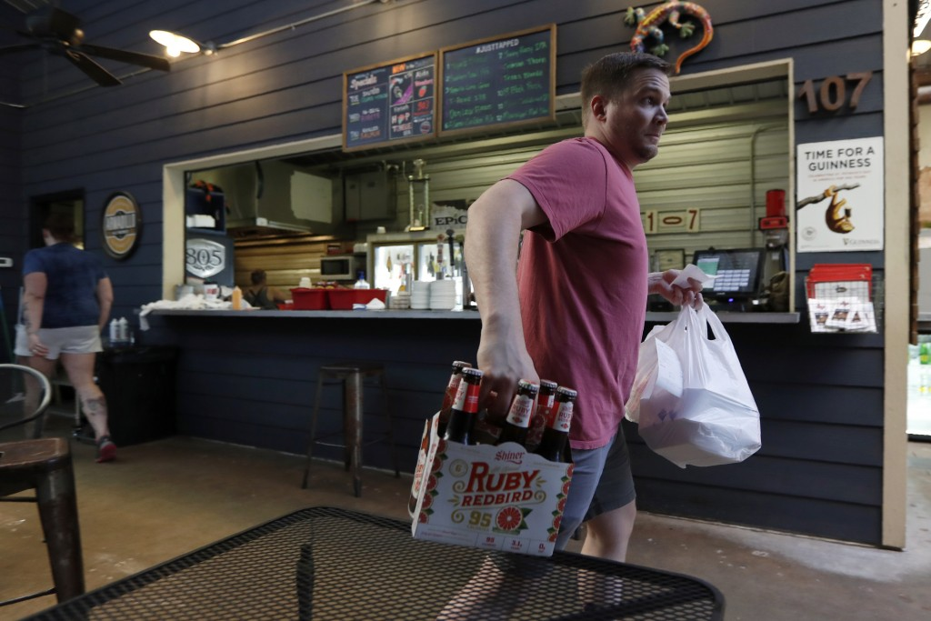 In this Wednesday, April 29, 2020, photo Cody Adams delivers a to-go order to a curbside customer at 107, a restaurant in Paris, Texas. The whiplash i...