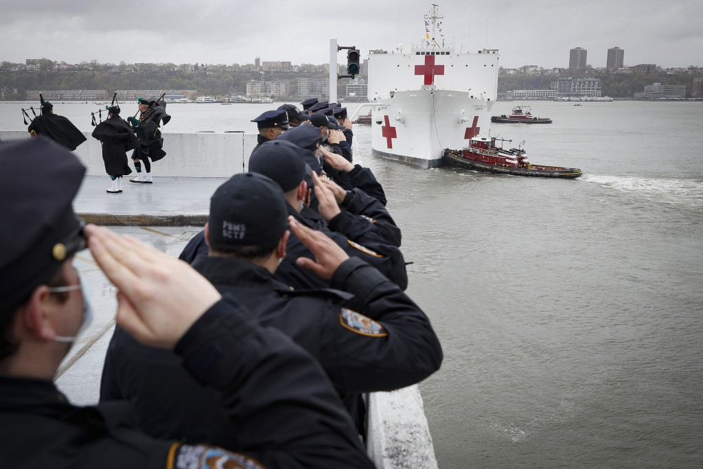 NYPD officers salute the USNS Naval Hospital Ship Comfort as it is pushed out into the Hudson River by tugboats, Thursday, April 30, 2020, in the Manh...