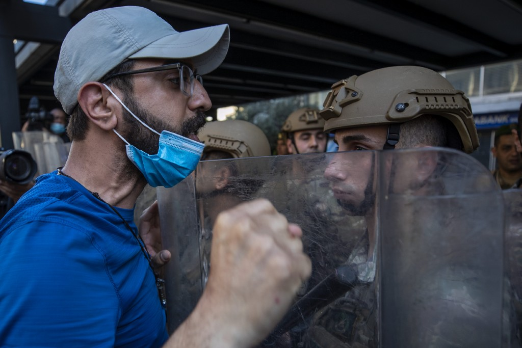 Army soldiers face off with an anti-government protester during May Day protests near the Lebanese Central Bank in Beirut, Lebanon, Friday, May 1, 202...
