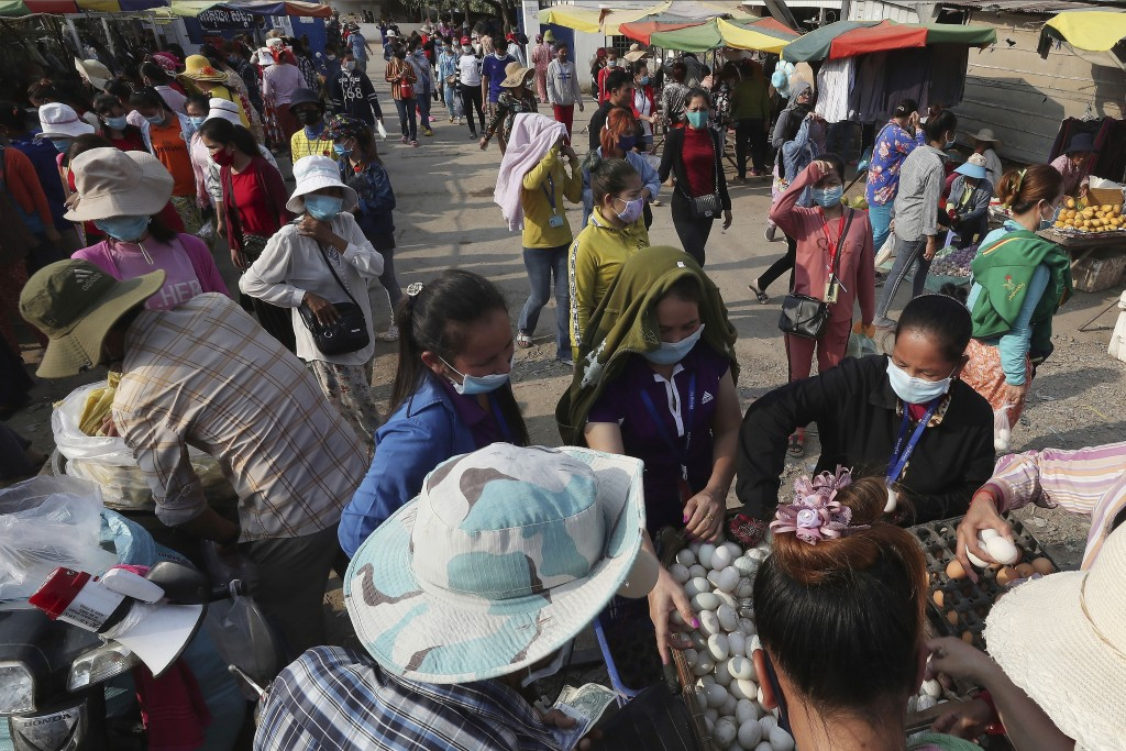In this March 20, 2020, photo, garment factory workers wear face masks as they buy food at the end of their work shift, near Phnom Penh, Cambodia. May...