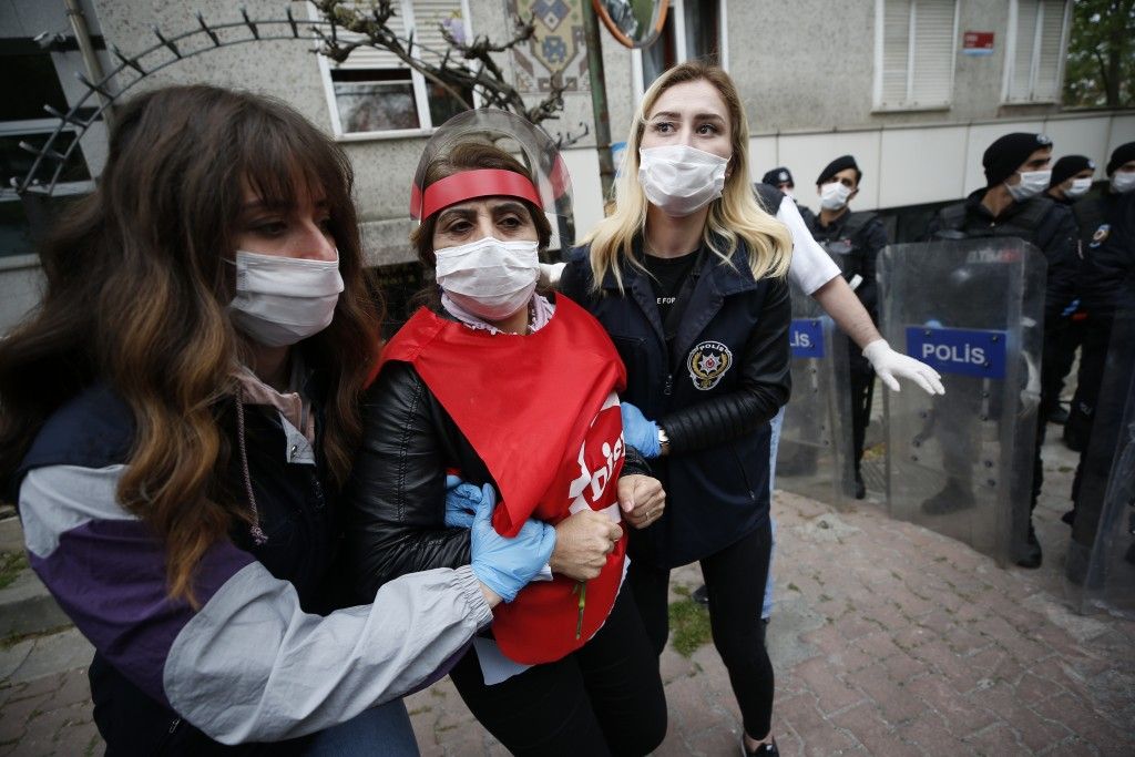 Turkish police officers, wearing face masks to protect against coronavirus arrest a demonstrator during May Day protests in Istanbul, Friday, May 1, 2...