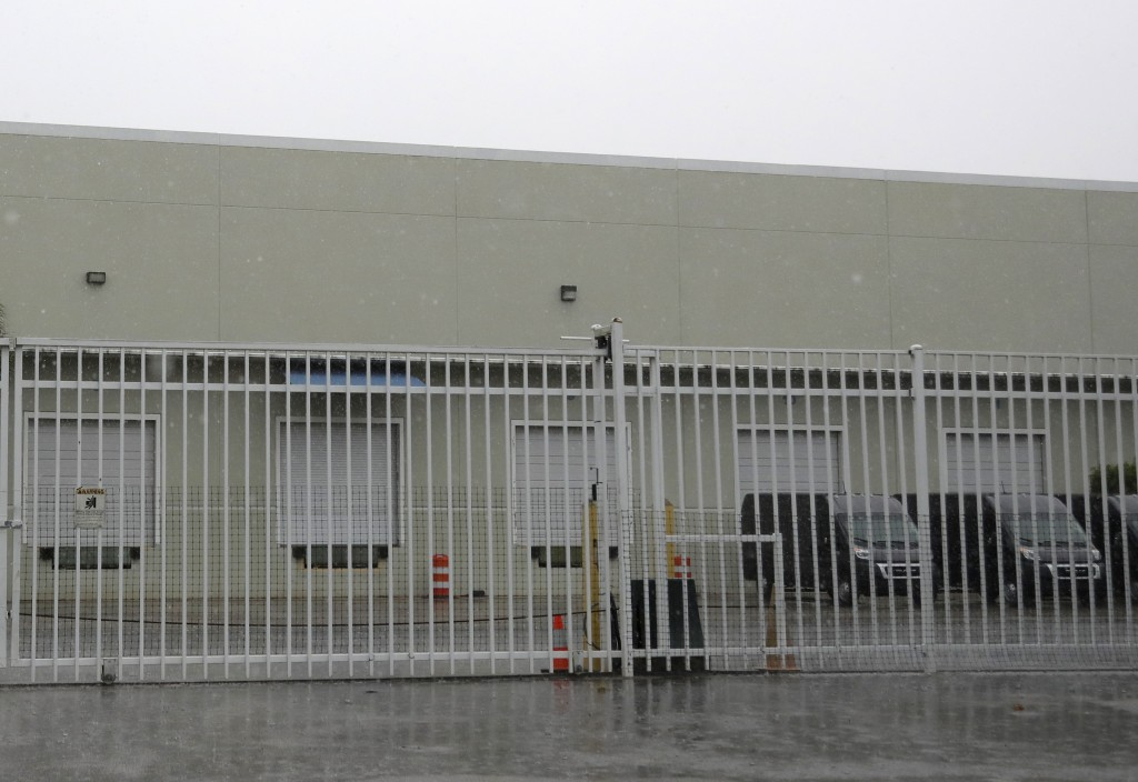 This Thursday, April 30, 2020 photo shows the gate outside a warehouse in Weston, Fla. used by the U.S. Drug Enforcement Agency. A DEA agent and a tel...