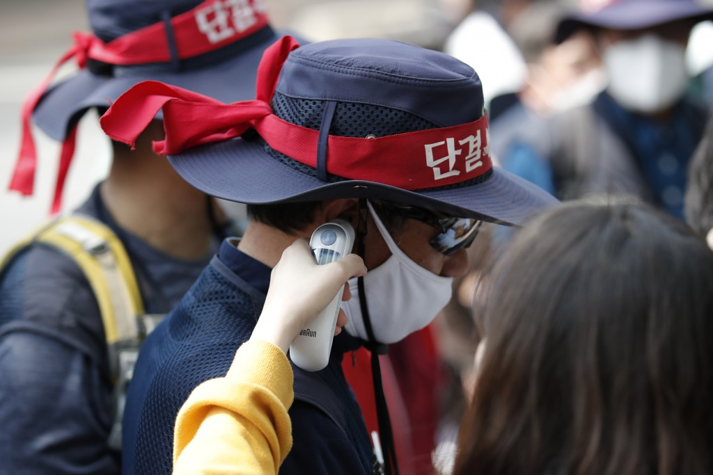 A member of the Korean Confederation of Trade Unions wearing face masks to help protect against the spread of the new coronavirus, has his temperature...