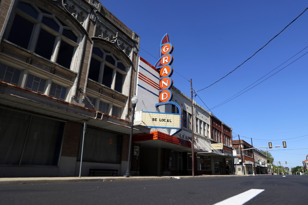 """In this Wednesday, April 29, 2020, photo a sign on the outside of the Grand, reads, """"Be Local,"""" off the town's square in Paris, Texas. The whiplash in..."""