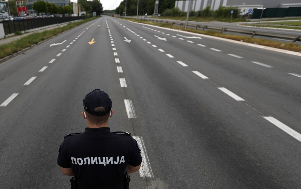 Police control traffic on the road during a curfew set up to help prevent the spread of the new coronavirus in Belgrade, Serbia, Friday, May 1, 2020. ...