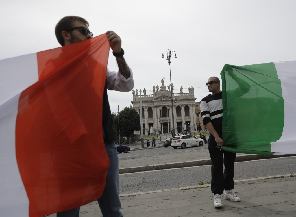 Far right militants show Italian flags as they protest for the right to demonstrate, in St. John at the Lateran Square, Friday, May 1, 2020. Italian P...