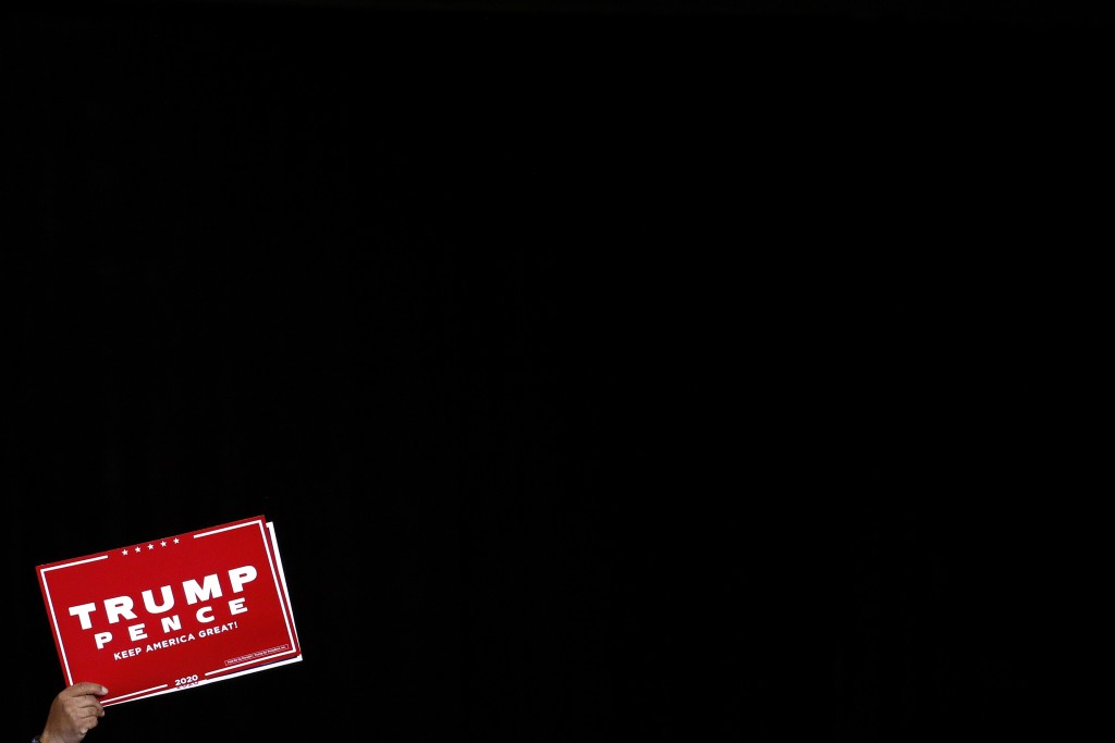 FILE - In this Feb. 21, 2020, file photo a supporter of President Donald Trump holds up a sign during a Trump campaign rally in Las Vegas. Six months ...
