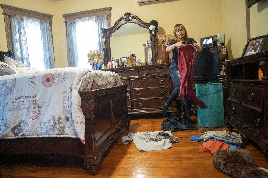 In this Monday, April 27, 2020 photo, Lissette Serrano sorts her laundry while doing her daily chores at home in Bridgeport, Conn., after being let go...