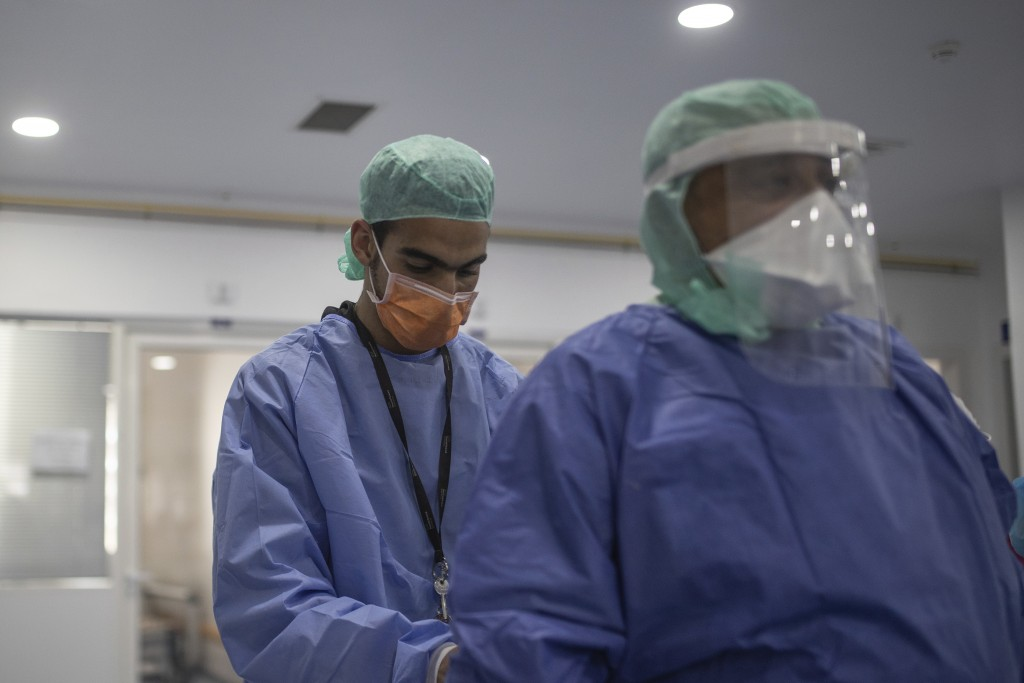 In this photo taken on Wednesday, April 15, 2020, healthcare workers assist each other inside one of the COVID-19 intensive care units (ICU) of the Mo...