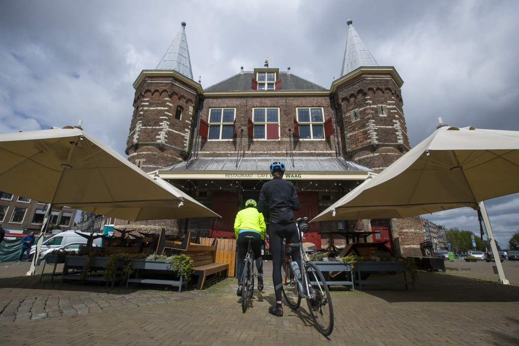 Customers wait to order lunch at the bike trough of restaurant cafe De Waag in Amsterdam, Netherlands, Saturday, May 2, 2020. The use of bicycles is a...