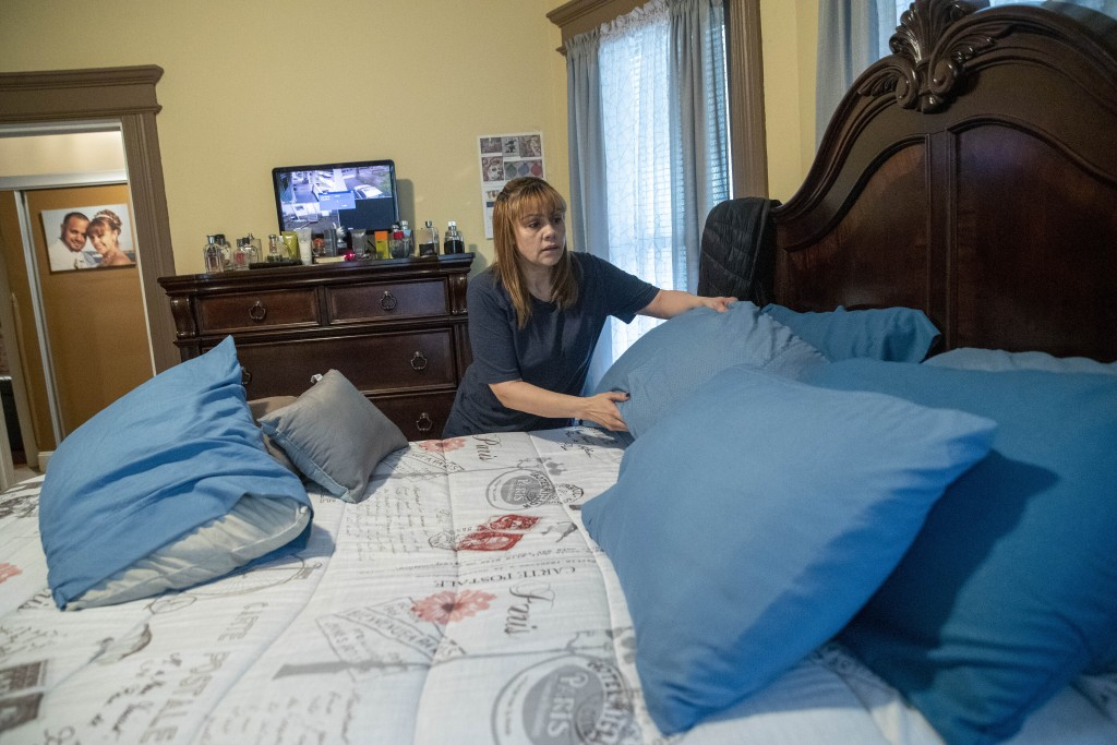 In this Monday, April 27, 2020 photo, Lissette Serrano makes her bed while doing her daily chores at home in Bridgeport, Conn., after being let go fro...