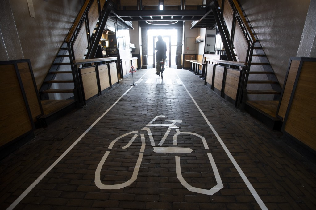 A customers leaves on his bicycle after ordering his lunch at the bike trough of restaurant cafe De Waag in Amsterdam, Netherlands, Saturday, May 2, 2...