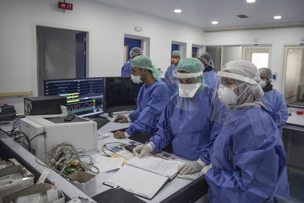 In this photo taken on Wednesday, April 15, 2020, healthcare workers monitor the situation of COVID-19 patients on a screen at one of the intensive ca...