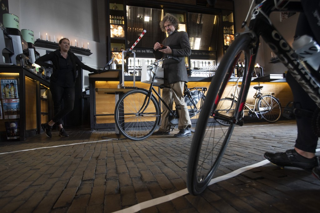 A customers puts his credit card back in his wallet after collecting his lunch at the bike trough of restaurant cafe De Waag in Amsterdam, Netherlands...