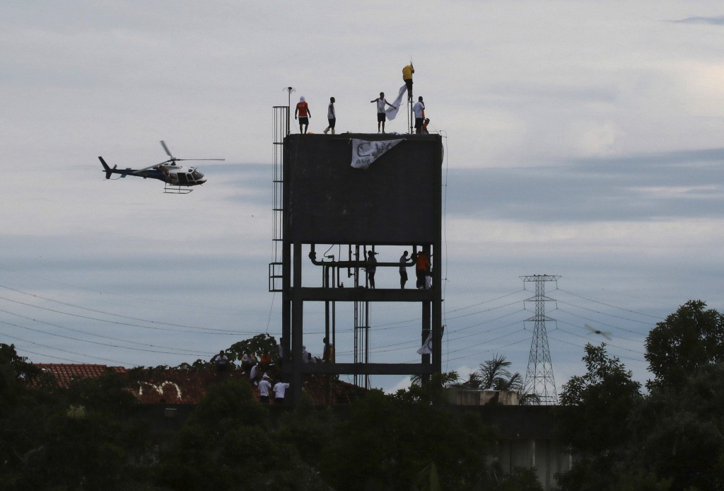 Military police fly over the Puraquequara prison as inmates stand on a water tower protesting against bad conditions and restrictions on family visits...