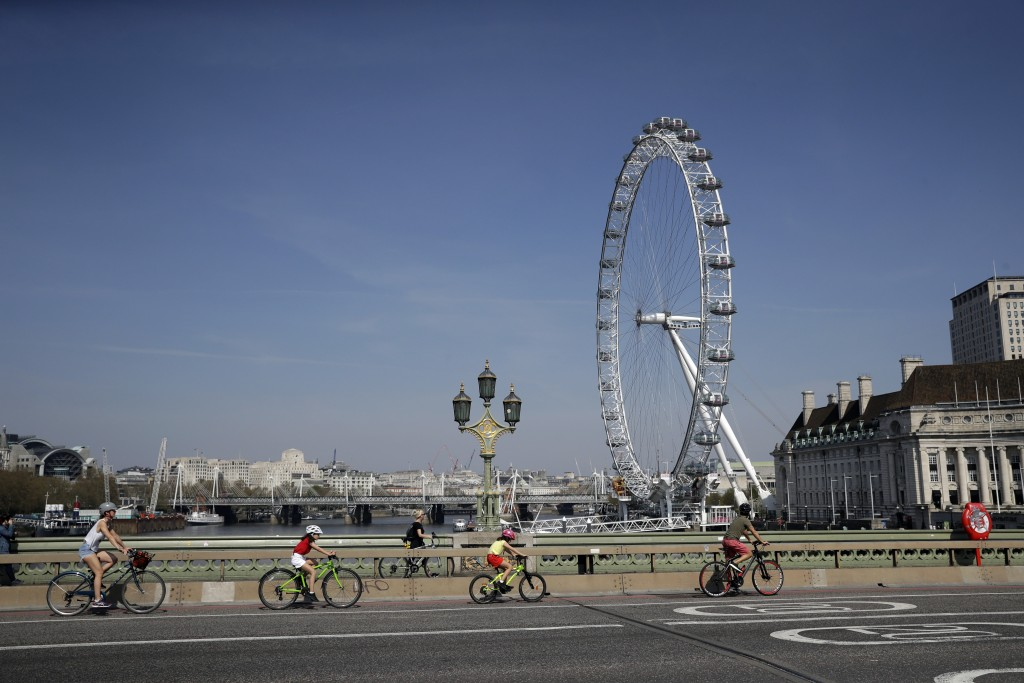 FILE - In this April 10, 2020, file photo, a family space themselves apart as they cycle over Westminster Bridge past the London Eye ferris wheel in L...
