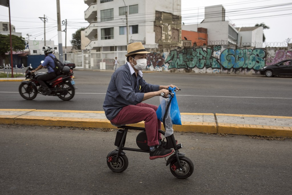 FILE - In this April 11, 2020, file photo, a man wearing a protective face mask as a precaution against the new coronavirus, rides on an electric bike...