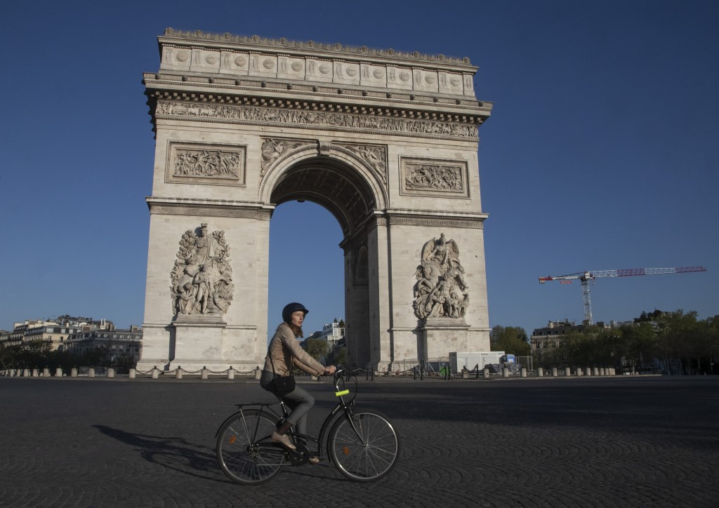 FILE - In this April 14, 2020, file photo, a woman rides a bike as she crosses the empty the Place Charles de Gaulle in Paris, during a nationwide con...