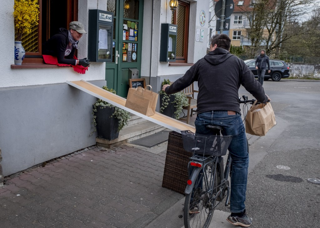FILE - In this April 3, 2020, file photo, a man on a bike picks up food to go in front of the apple cider restaurant 'Zum Lahmen Esel' in Frankfurt, G...