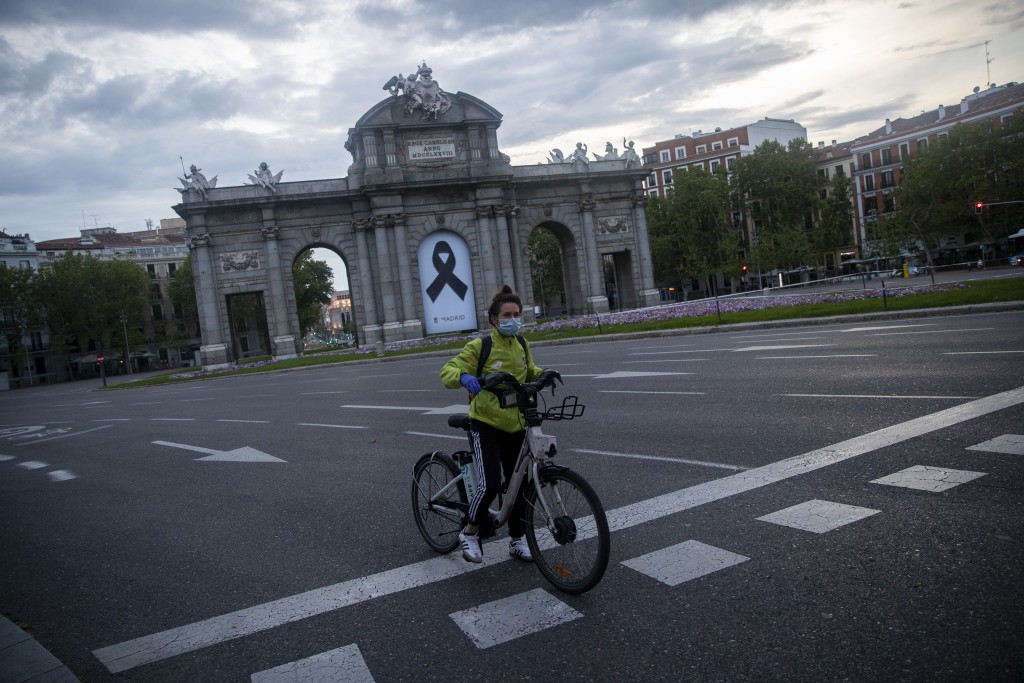 In this photo taken on Saturday, April 25, 2020, a woman rides Madrid's electric bike hire service BiciMAD in front of a Puerta de Alcala square with ...