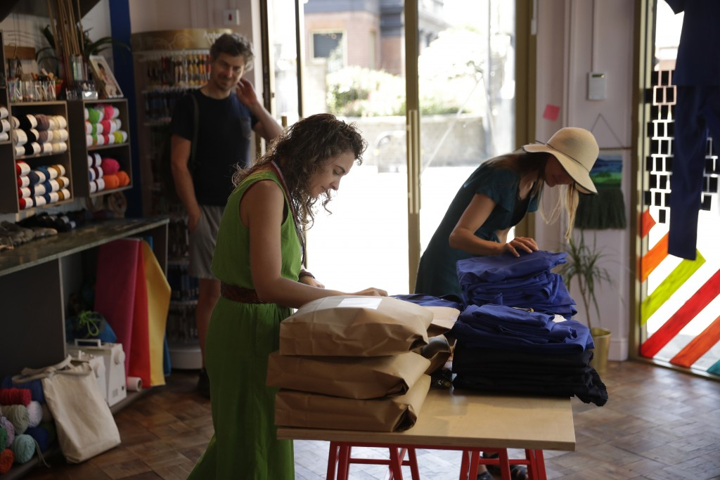 Textile artist Brooke Dennis, centre, who is originally from New Zealand, receives scrubs made for NHS (National Health Service) staff to wear during ...