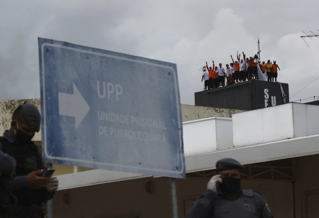 Military police secure the perimeters of the  Puraquequara prison as inmates stand on a water tower protesting against bad conditions and restrictions...