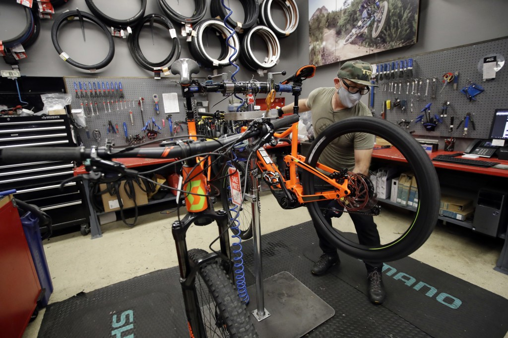 In this Wednesday, April 29, 2020, photo, bike mechanic Ivan Harms prepares two bikes after they were sold amid the new coronavirus pandemic, at Incyc...