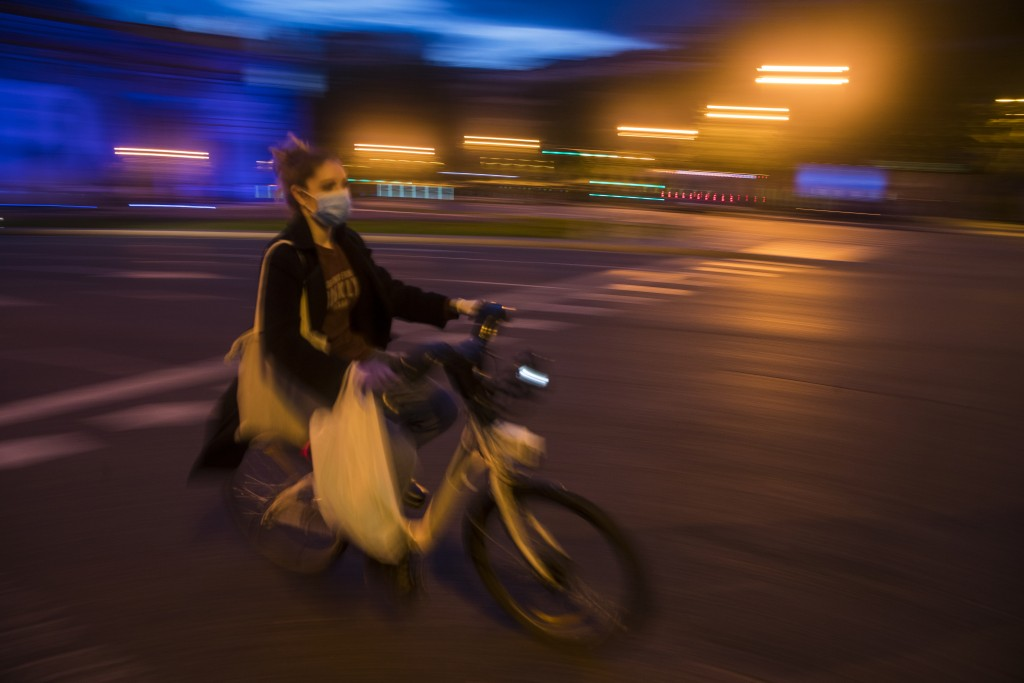 In this photo taken on Saturday, April 25, 2020, a woman rides a Madrid's electric bike hire service BiciMAD as the lockdown to combat the spread of c...