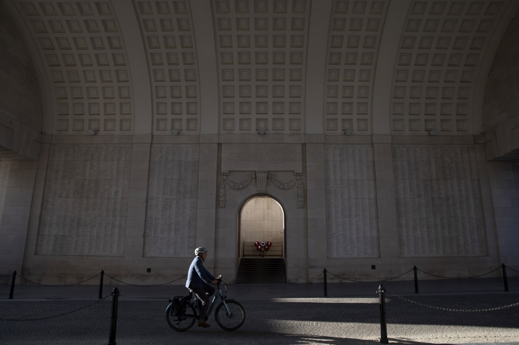 In this April 25, 2020, a man cycles under the World War I monument, Menin Gate, in Ypres, Belgium. As countries across the world seek to get their ec...