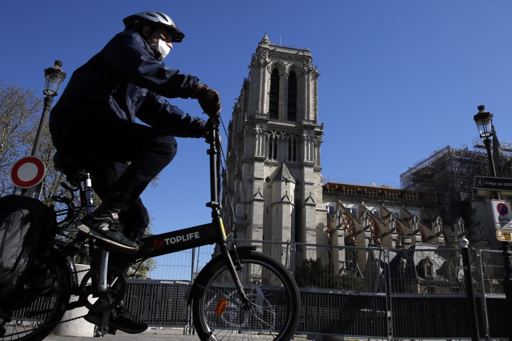 FILE - In this April 5, 2020, file photo, a man wearing a face mask rides his bike in front of Notre Dame cathedral during a nationwide confinement to...