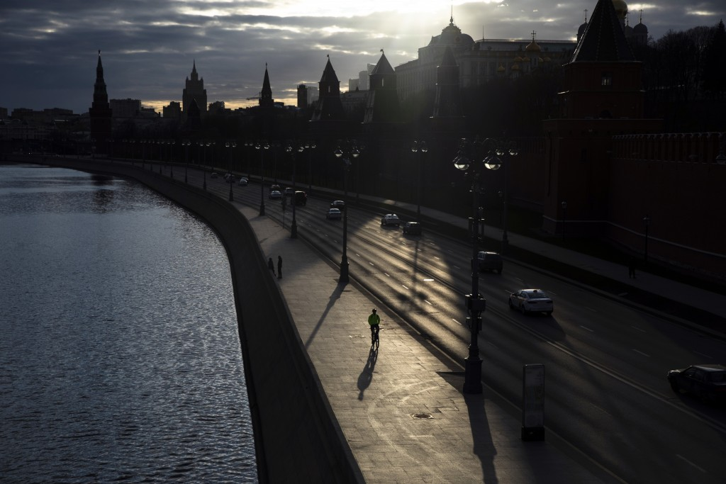 In this April 10, 2020, photo, a man rides a bike along the embankment of the Moskva River in front of the Kremlin in Moscow, Russia. As countries acr...