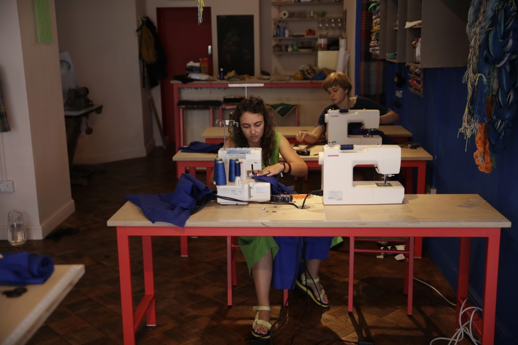 Textile artist Brooke Dennis, left, who is originally from New Zealand, makes scrubs for NHS (National Health Service) staff to wear during the corona...