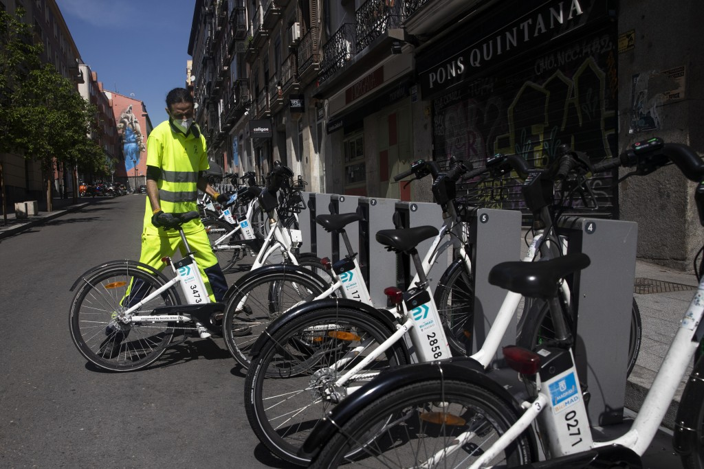 In this photo taken on Saturday, April 25, 2020, a staff member removes a Madrid's electric bike hire service BiciMAD as the lockdown to combat the sp...