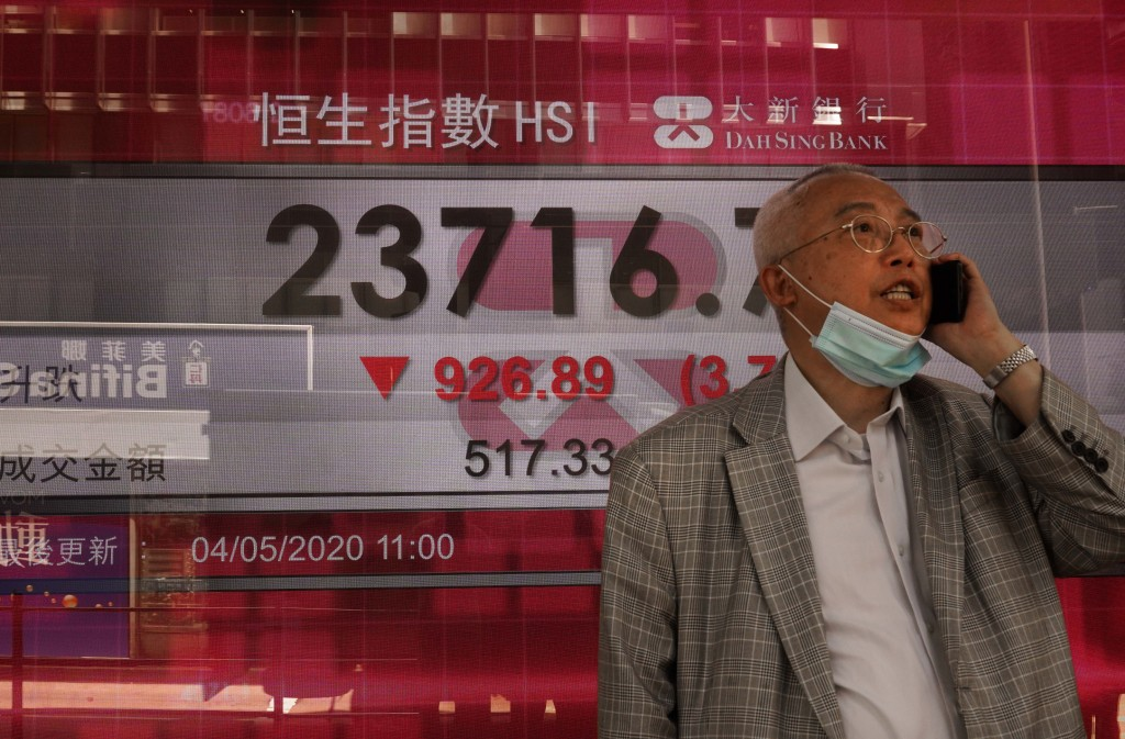 A man wearing face mask walks past a bank electronic board showing the Hong Kong share index at Hong Kong Stock Exchange Monday, May 4, 2020. Shares h...