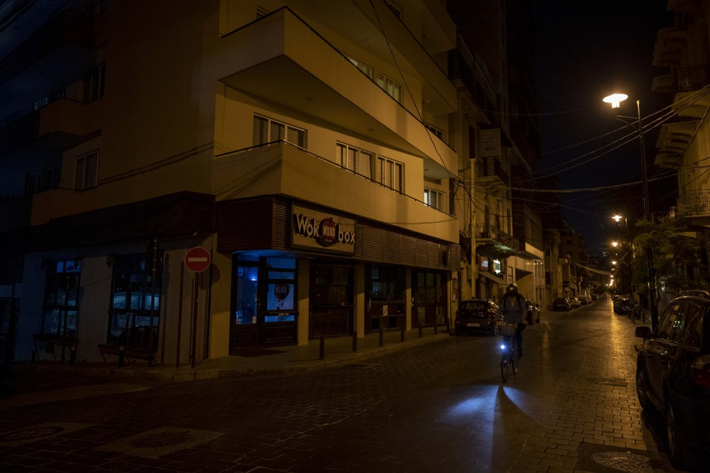 A woman rides her bike past a number of closed bars along a major nightlife hub during the coronavirus pandemic, in central Beirut, Lebanon, Sunday, M...