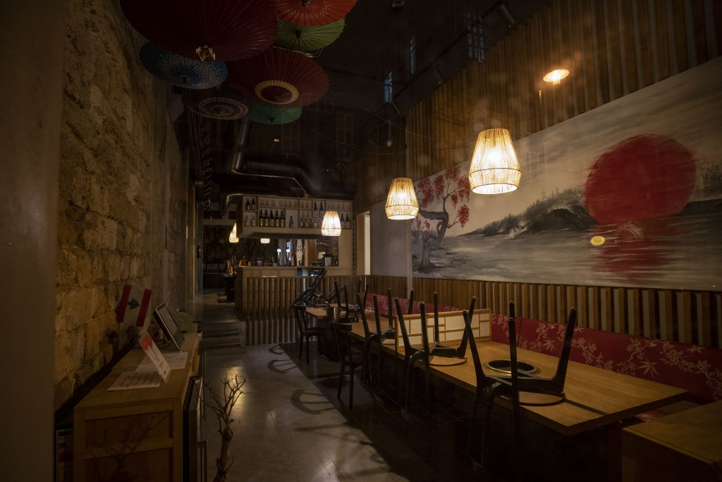 In this Sunday, May 3, 2020 photo, chairs are placed on tables in a closed restaurant during the coronavirus pandemic in a major nightlife hub, in cen...