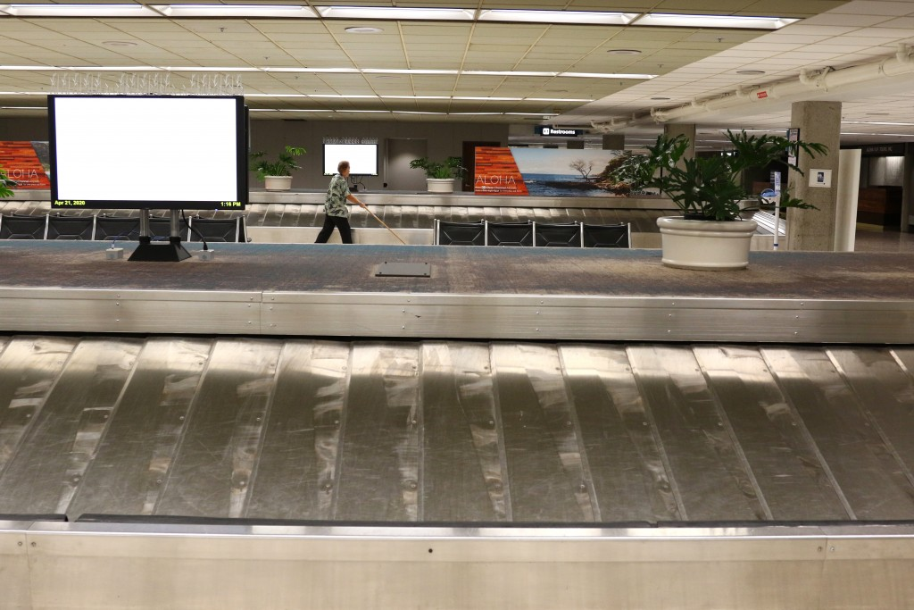 In this April 21, 2020, photo, a worker cleans the baggage claim area at the international airpot in Honolulu. Hawaii has some of the lowest coronavir...
