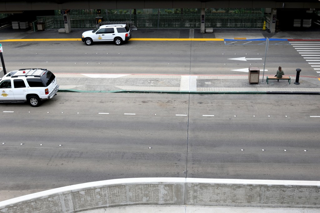 In this April 21, 2020, photo, a woman sits alone on a bench in a normally busy area of Honolulu's international airport. Hawaii has some of the lowes...