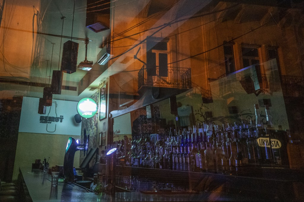 In this Sunday, May 3, 2020 photo, balconies of an old building are reflected in the glass door of a closed bar during the coronavirus pandemic, in ce...