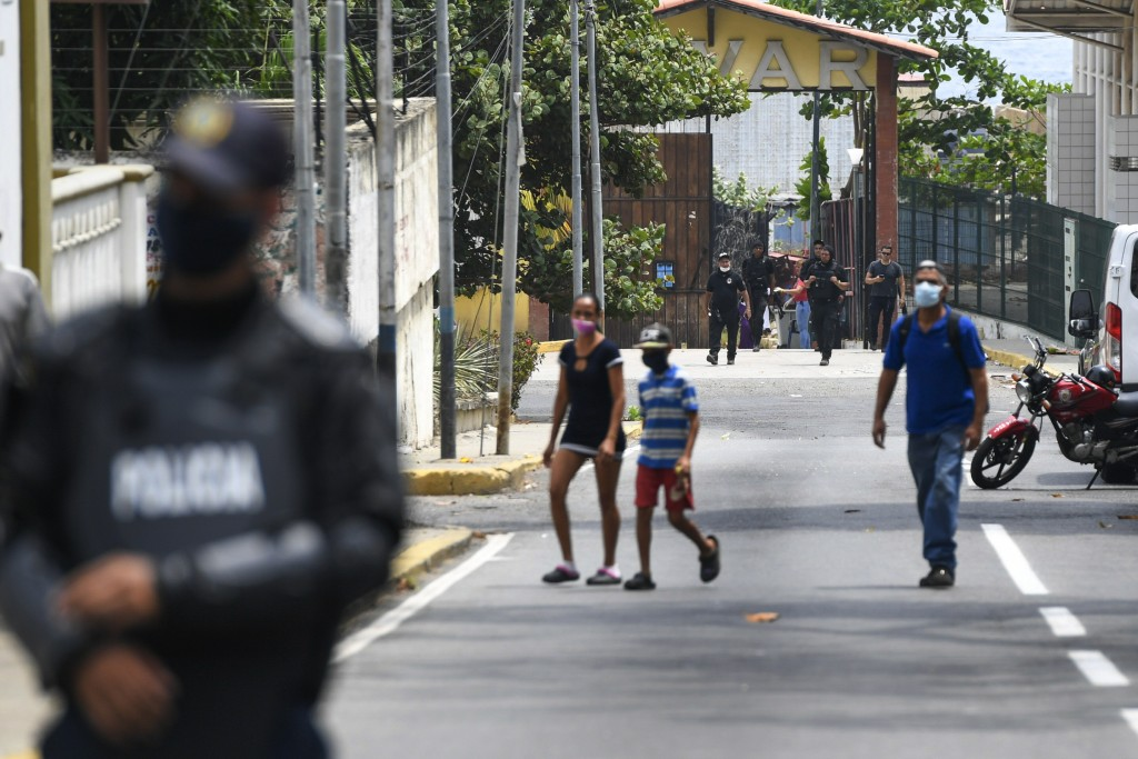 Security forces, back, leave a facility in the Macuto area in La Guiara, Venezuela, Sunday, May 3, 2020. Interior Nestor Reverol said on state televis...