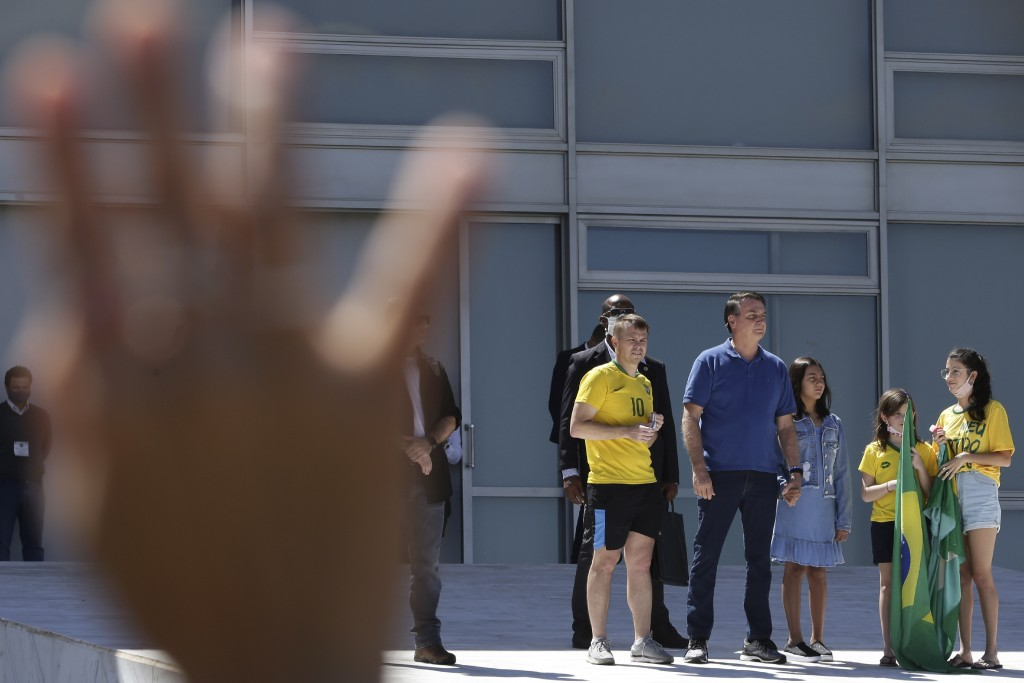 Brazil's President Jair Bolsonaro (blue shirt) and his daughter attend a protest against his former Minister of Justice Sergio Moro and the Supreme Co...