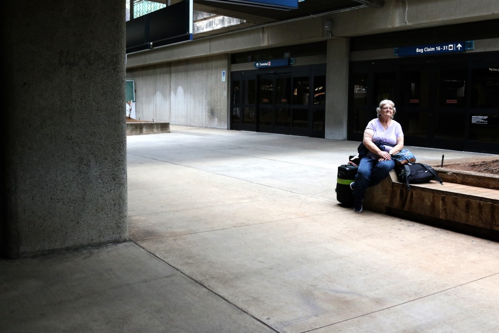 In this April 21, 2020, photo, Hawaii resident Mary Ann Jenkins waits for her ride after arriving home from Indiana at the international airport in Ho...
