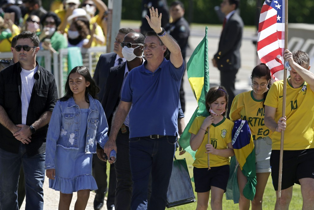 Brazil's President Jair Bolsonaro holds his daughter's hand as he waves to supporters during a protest against his former Minister of Justice Sergio M...