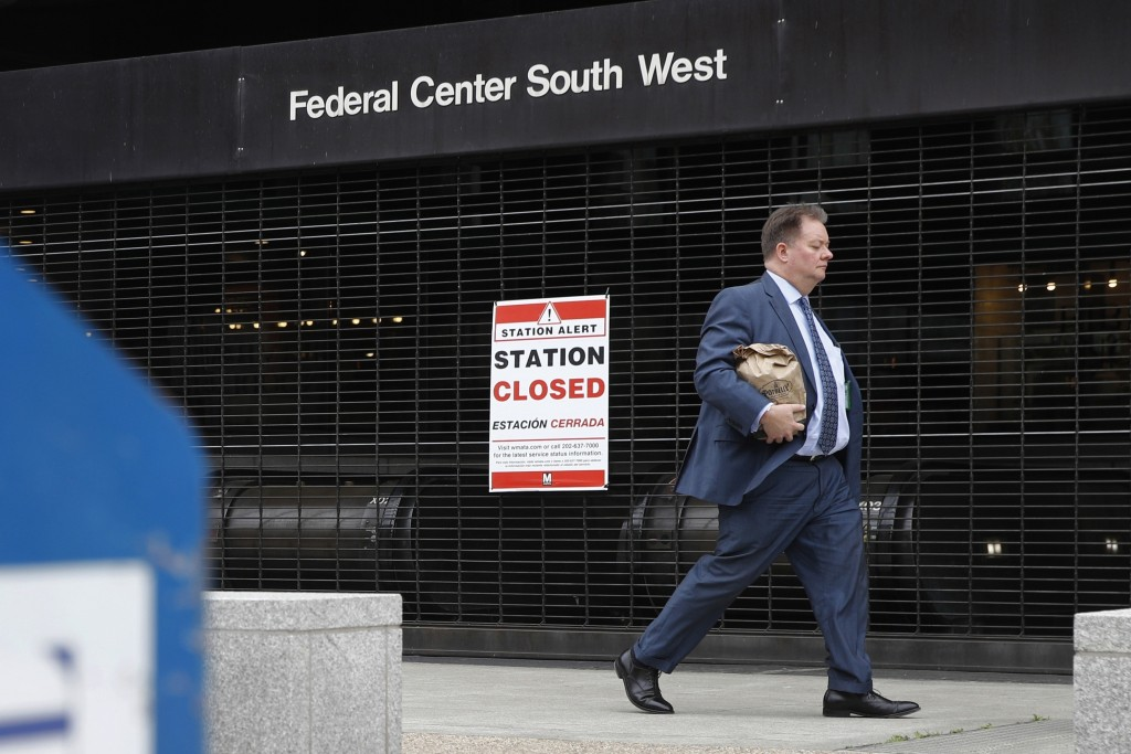FILE - In this March 31, 2020, file photo, a man walks past Metro's Federal Center Southwest station, closed due to reduced ridership in response to t...