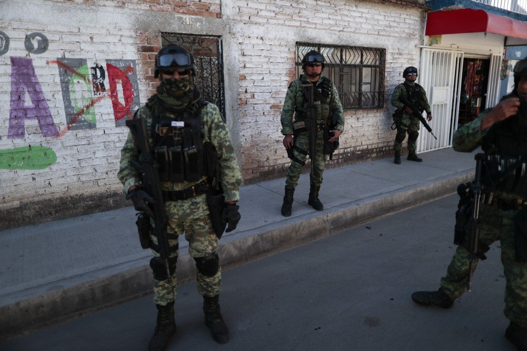 FILE - In this Feb. 12, 2020 file photo, soldiers patrol a neighborhood in Irapuato, Guanajuato state, Mexico. Mexico's drug war has long played out i...