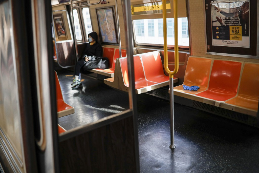 FILE - In this April 7, 2020, file photo, a pair of discarded gloves rests on an empty seat as a rider, wearing a protective mask, rides the New York ...