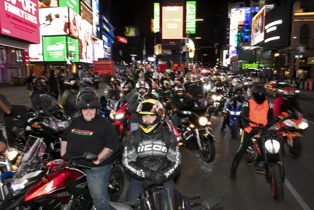 In this Saturday, May 2, 2020 photo, dozens of motorcyclists stop for photos in New York's Times Square during the coronavirus pandemic. Motorcycle en...